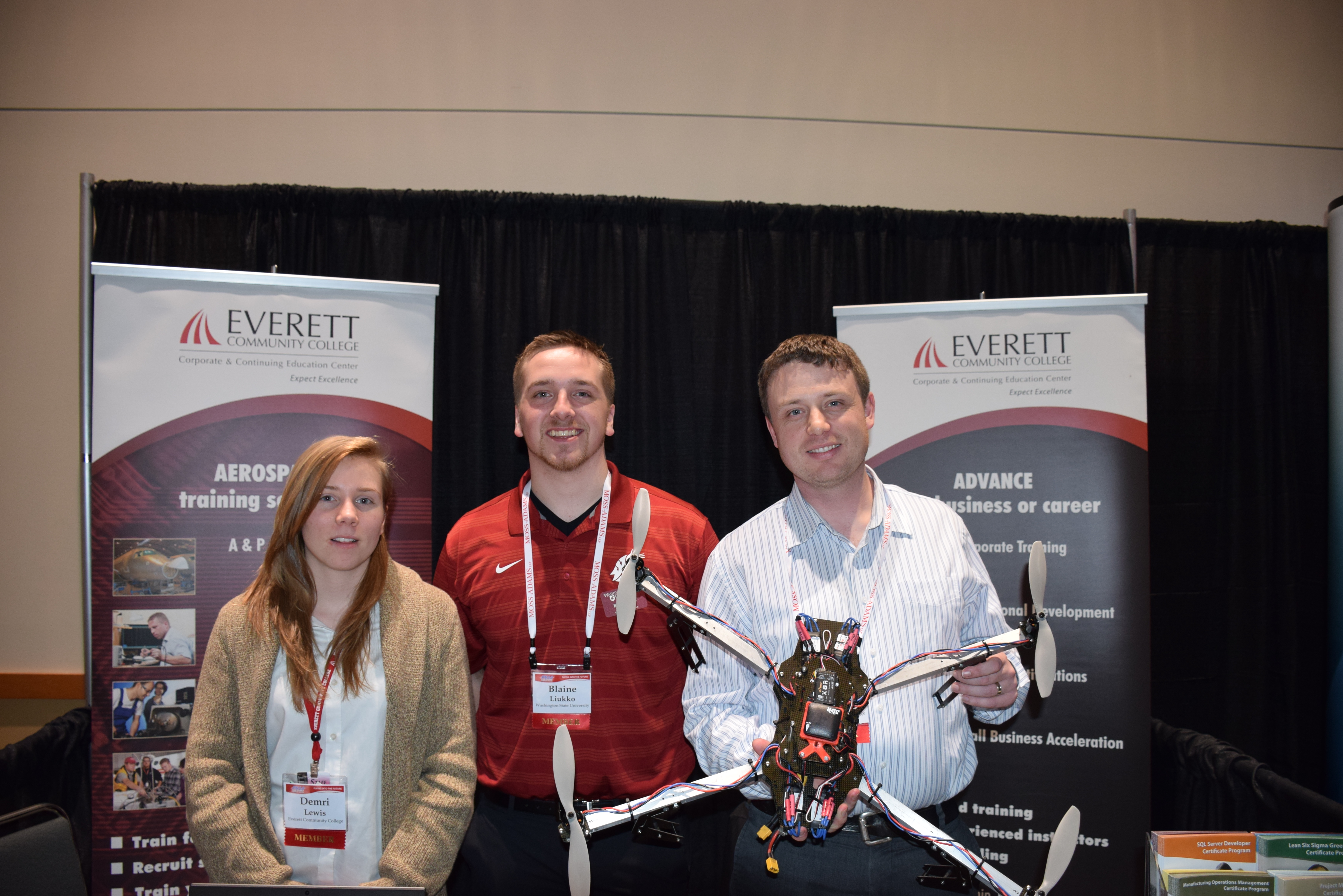 Students from Everett Community College and WSU show off a UAS that they built (Thor Nelson, profiled, is holding the UAS on the right; Demri Lewis and Blain Liukko left - right).